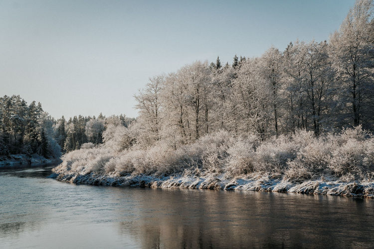Scenic view of river against clear sky during winter