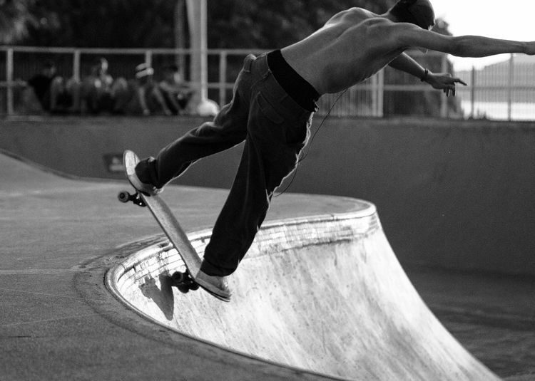 Rear view of teenage boy skateboarder jumping at skatepark