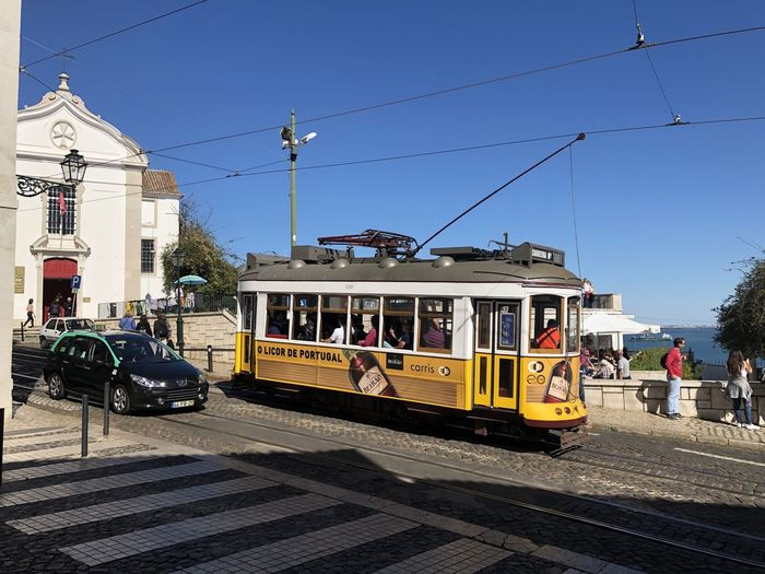Street tram in Lisbon, Portugal Lisbon Portugal Transportation Mode Of Transportation Public Transportation Track Sky Railroad Track Rail Transportation Day Cable Car Land Vehicle Nature City Architecture Building Exterior Built Structure Clear Sky Sunlight Street Cable Incidental People Electricity  Outdoors