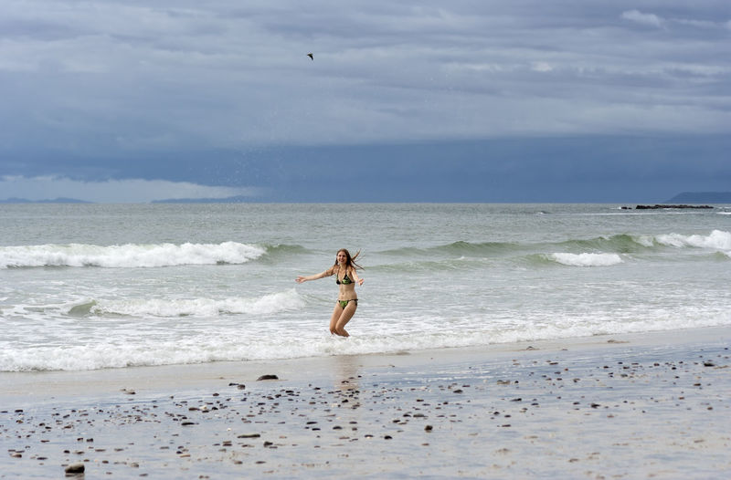 Mid adult woman in bikini standing on shore against sky