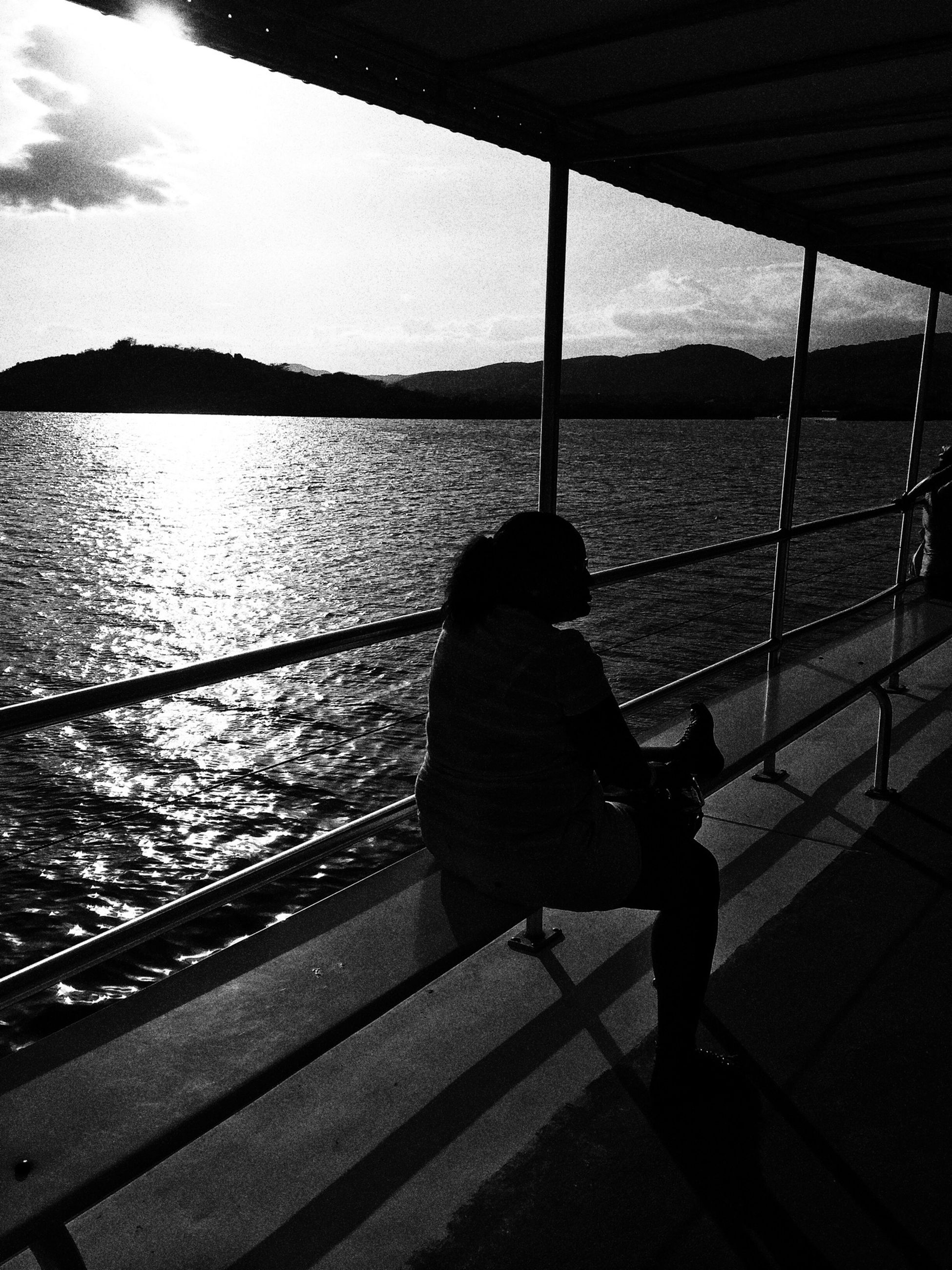 rear view, water, lifestyles, leisure activity, silhouette, men, standing, full length, person, reflection, lake, shadow, river, railing, walking, sunlight, sky, outdoors