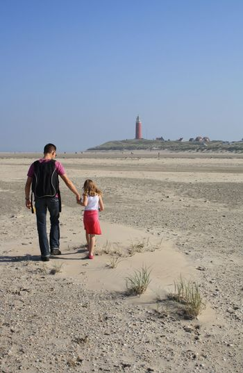 Rear view of father with daughter walking at beach against clear sky