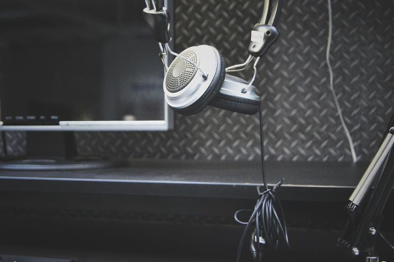 Close-Up Of Headphones And Television At Recording Studio
