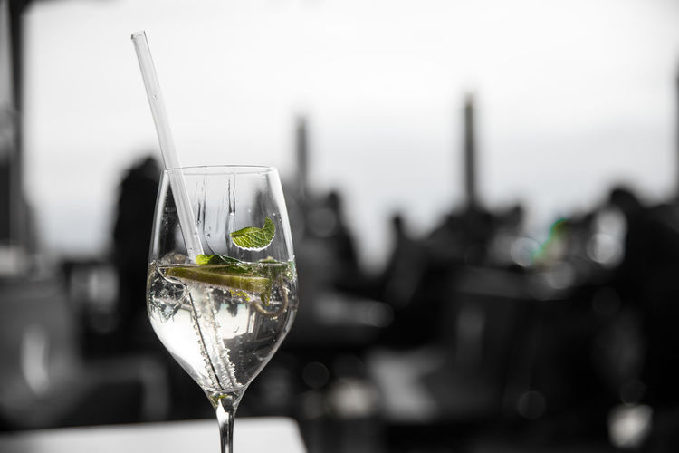 a glass of cocktail Refreshment Drink Glass Food And Drink Alcohol Focus On Foreground Household Equipment Drinking Glass Glass - Material Close-up Transparent Wineglass Freshness Food No People Table Day Still Life Outdoors Mint Leaf - Culinary Cocktail Mojito