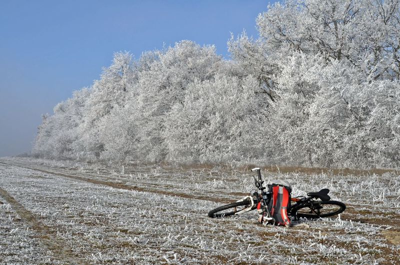 Bicycle on field against sky during winter
