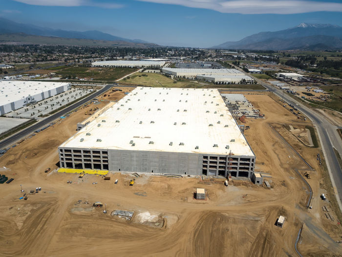 Beaumont, CA / USA - 4/20/2019: Overhead view of a new Amazon Fulfillment Center under construction. High Angle View Day Architecture Built Structure No People Outdoors Construction Construction Site Warehouse Distribution Logistics Equipment New Building  Amazon Overhead View Environment Landscape Land Nature Mountain Industry Scenics - Nature Aerial View Field Sky Transportation Beauty In Nature Tranquil Scene Fuel And Power Generation Pollution