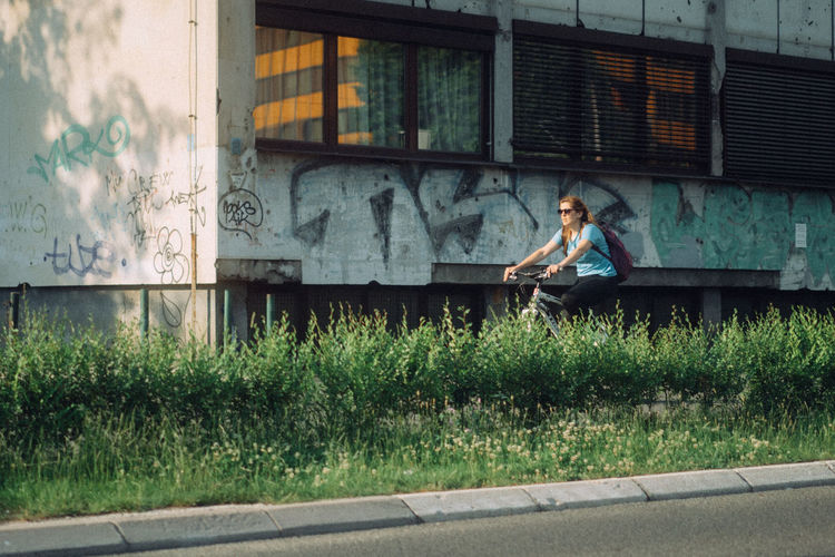 Woman using mobile phone while sitting on window