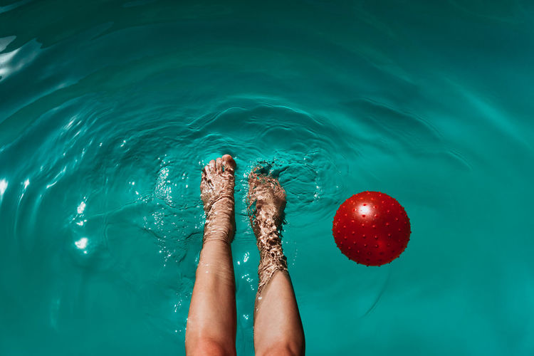 Low section of woman with ball swimming in pool