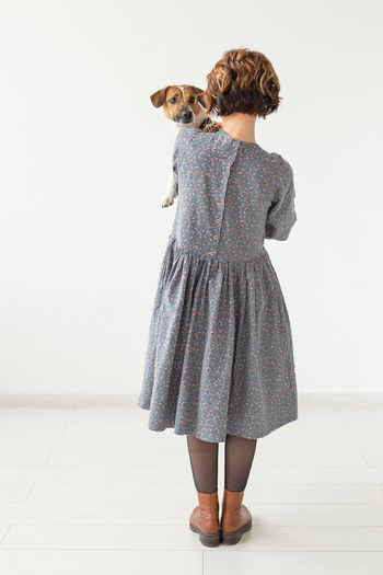 Rear view of woman standing on small wall