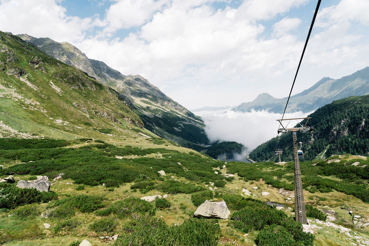 Overhead cable car on mountains against sky