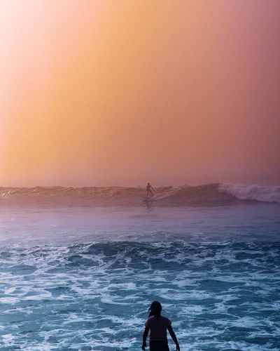 Man standing on sea against sky during sunset