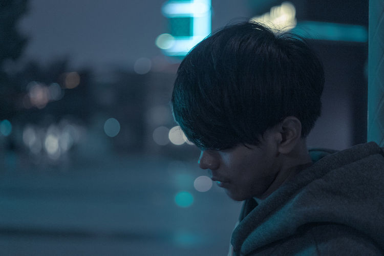 Close-up portrait of boy looking away at night