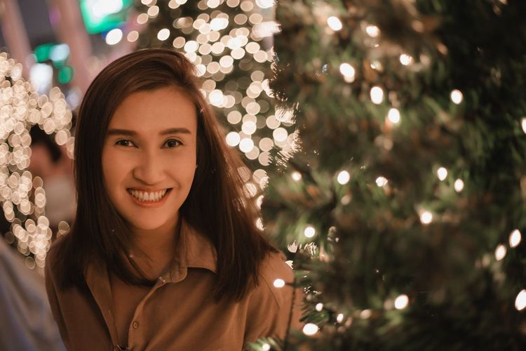 Portrait of smiling woman with christmas tree at night