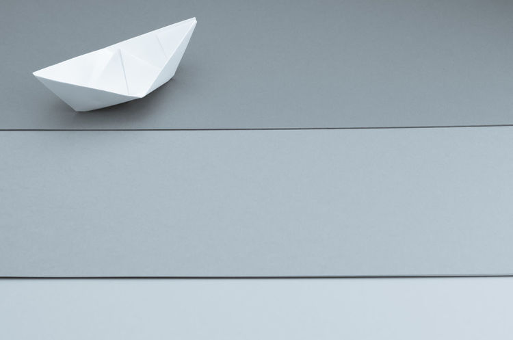 paper sailboat Art And Craft Clean Close-up Copy Space Craft Creativity Day Design Floating Floating On Water Folded Gray Indoors  Minimalism No People Origami Paper Paper Airplane Paper Boat Paperwork Sailboat Shape Still Life Wall - Building Feature White Color