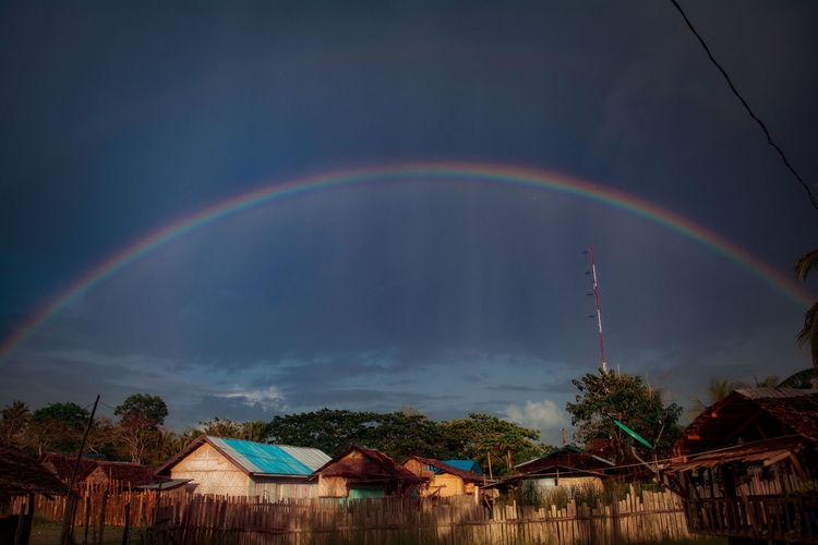 Rainbow over buildings against sky
