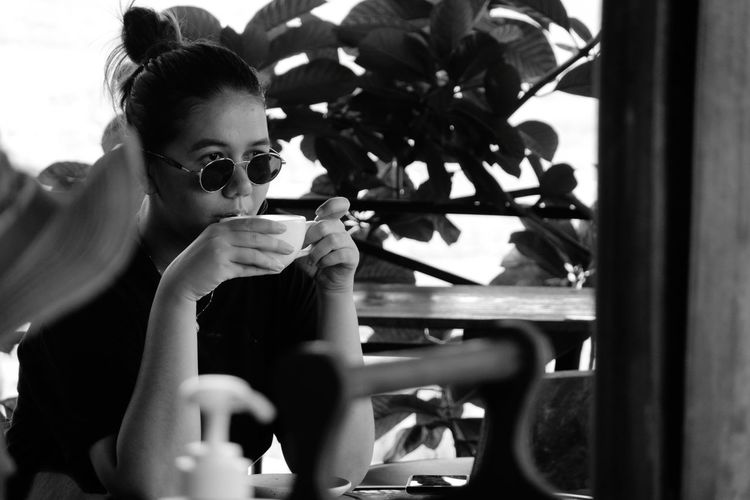Portrait of young woman holding coffee while sitting on window