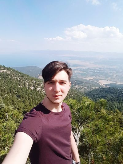 Portrait of young man against mountain range