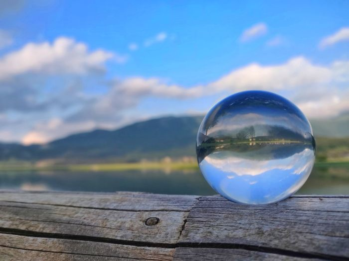 Close-up of water ball on wood against sky