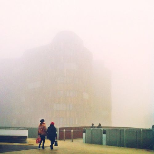 Full length rear view of woman standing in foggy weather