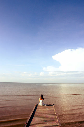 Rear view of woman sitting on pier over sea at beach