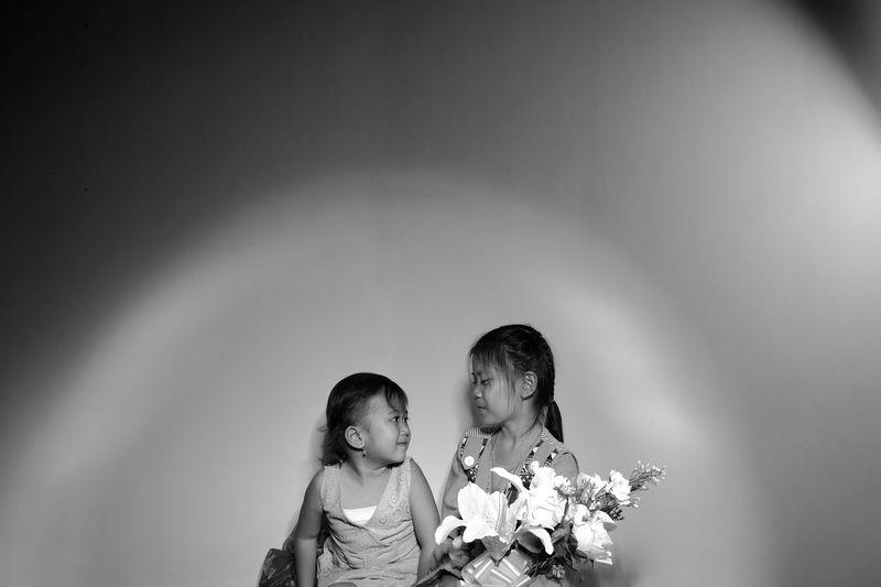 Girls sitting against wall