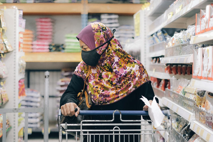Woman wearing mask and shopping in store