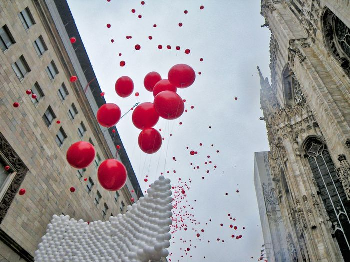 Low angle view of balloons hanging on building against sky