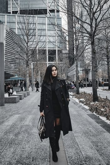 Woman with umbrella in city during winter