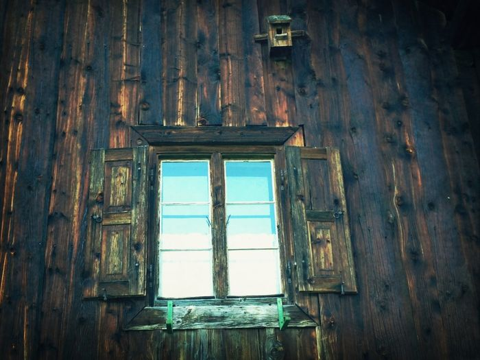 Low angle view of open window on wooden cabin