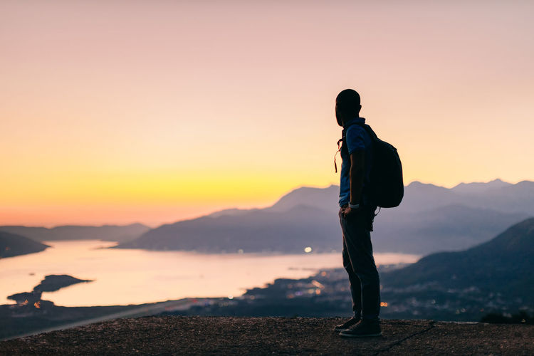 Side view of man standing on mountain against sky during sunset