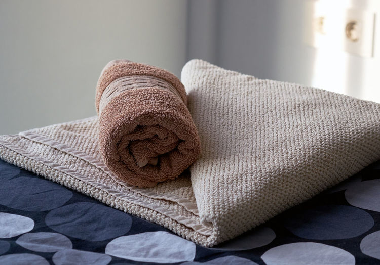Close-up of rolled up towel on bed at home