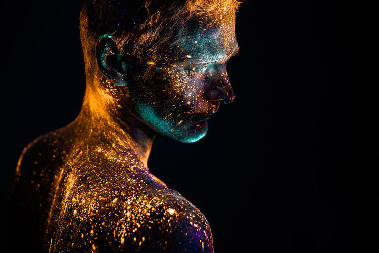 Close-up of shirtless male model with powder paint against black background