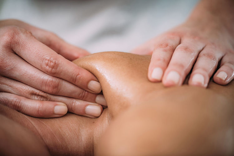 Cropped hands of massage therapist massaging female customer in spa