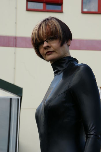 Portrait of woman in latex clothing standing against building