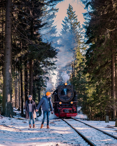 Couple standing on railroad tracks during winter
