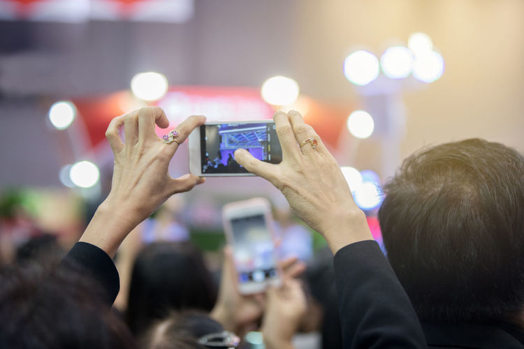 Close-up of woman photographing music concert