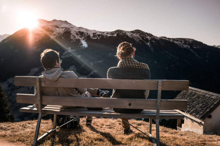Rear View Of Friends Sitting On Bench Against Mountains During Sunset