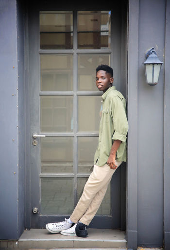 Side view of young man standing at entrance of building