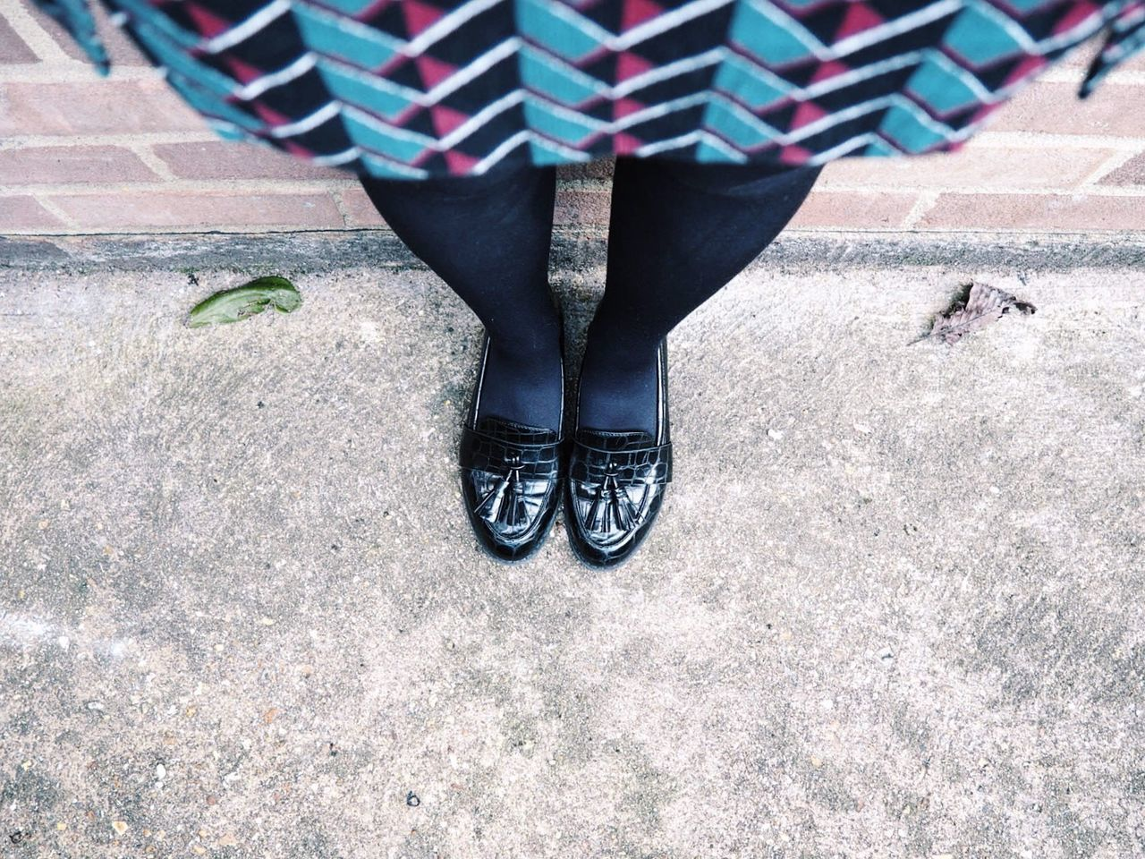 Low section of woman wearing black shoes standing on footpath