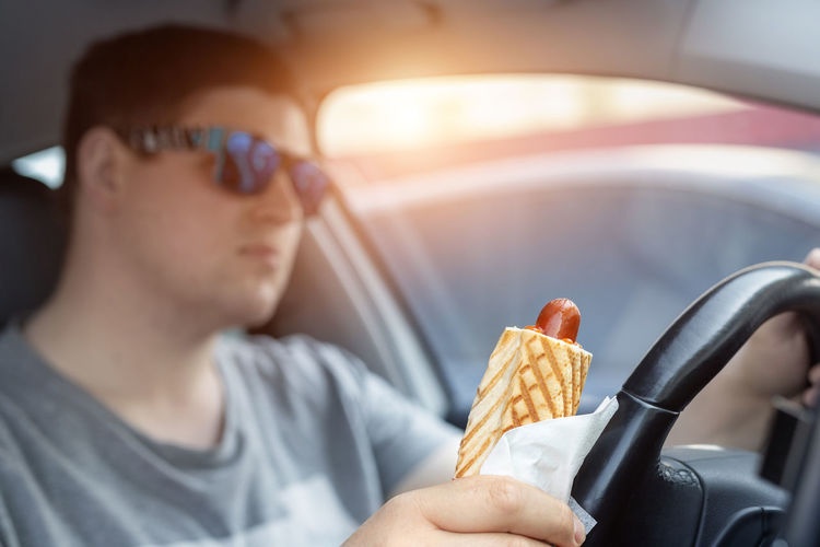 Man holding food while driving car