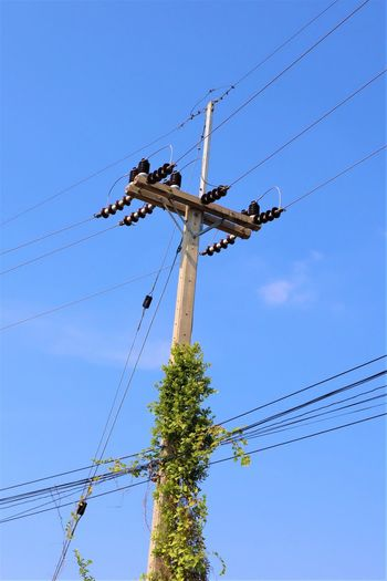 Low angle view of power line against blue sky