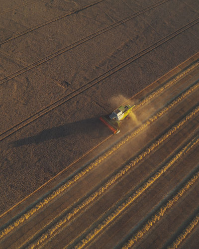 High angle view of agricultural field with harvester
