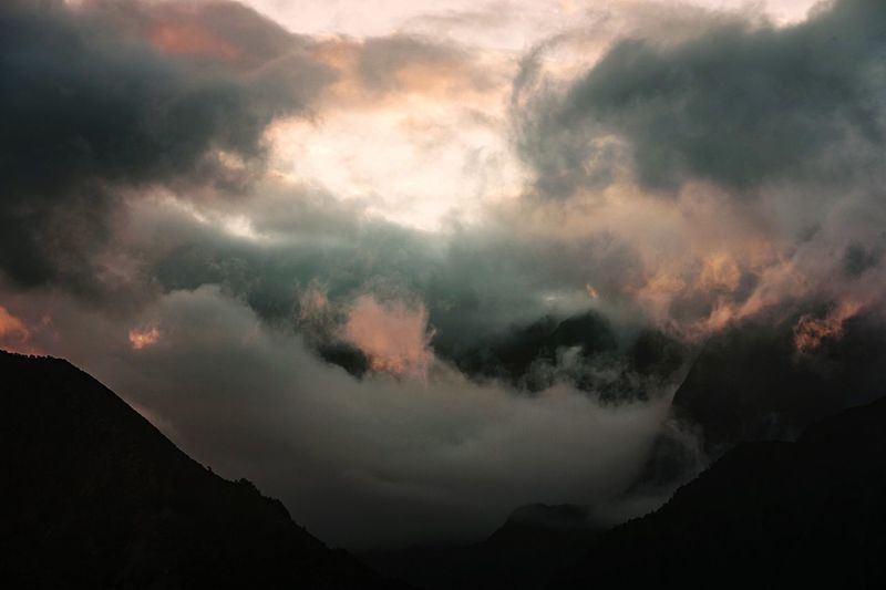 Scenic view of clouds over silhouette mountains against sky