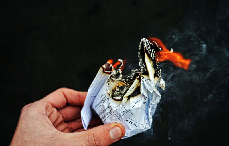 Cropped hand holding burning paper against black background