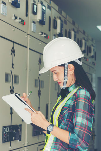 women engineer working on checking and maintenance electrical equipment ;women engineer checking status switchgear with checklist Assembly, Breaker, Business, Check, Checklist, Circuit, Communication, Connect, Control, Current, Devices, Diagram, Effect, Efficiency, Electric, Electrician, Energy, Engineer, Equipment, Expertise, Gear, Girl, Industrial, Industry, Inspector, Interlock, Labor, Machine, Maintenance, Measurement, Monitor, Operation, Performance, Power, Professional, Quality, Reliability, Safety, Service, Smart, Solution, Substation, Switch, System, Technician, Technology, Vacuum, Voltage, Women, Work