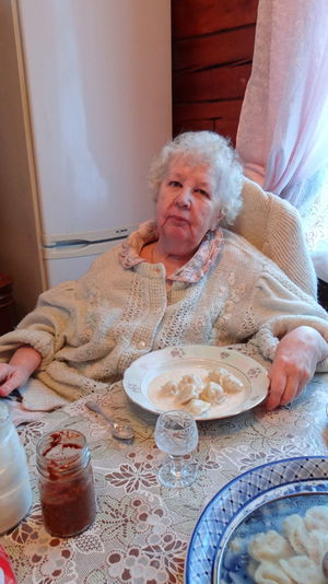 Portrait Of Senior Woman With Dumplings Sitting By Table At Home