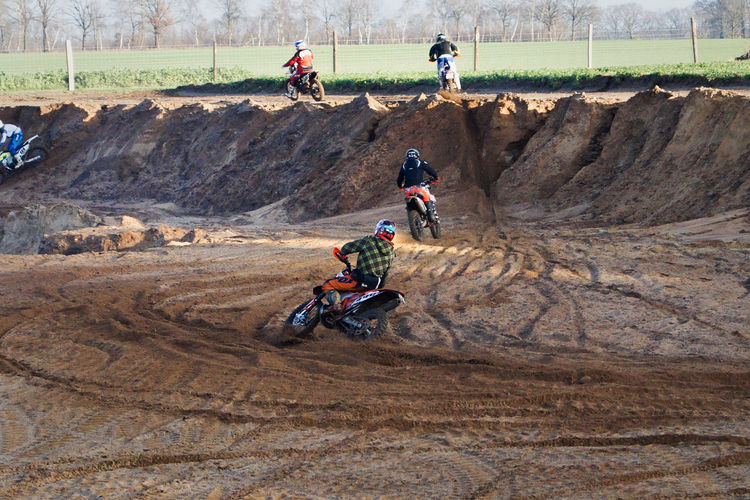 People riding motocross on field