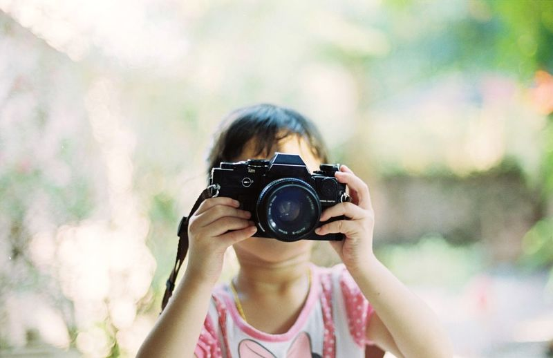 Little girl holding a camera Camera Kids Girl Little Girl Camera - Photographic Equipment Photography Themes Photographing Activity One Person Technology Portrait Holding Headshot Front View Child Childhood Photographer Offspring Photographic Equipment Women Casual Clothing Occupation Focus On Foreground Digital Camera