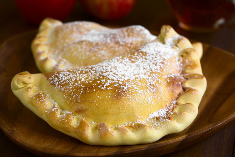 Chilean apple empanada with icing sugar, photographed on dark wood with natural light (Selective Focus, Focus one third into the image) Apple Breakfast Chile Chilean  Empanadas Filled Horizontal Latin American Food  South American Food Stuffed Apple Empanada Baked Chilean Food Dessert Empanada Food Food And Drink Fruit Icing Sugar Pastry Powdered Sugar Snack Sugar Sweet Sweet Food