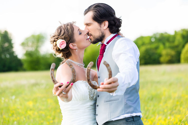 Couple holding horseshoes and kissing while standing outdoors